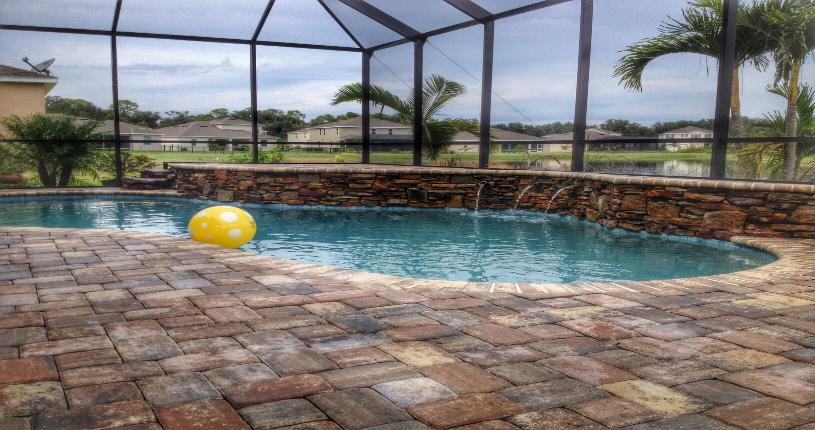 Swimming pool in Parrish with stonework and landscaping
