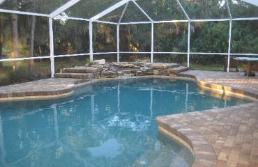remodeled pool with pebble tec, pavers, and natural stone waterfall